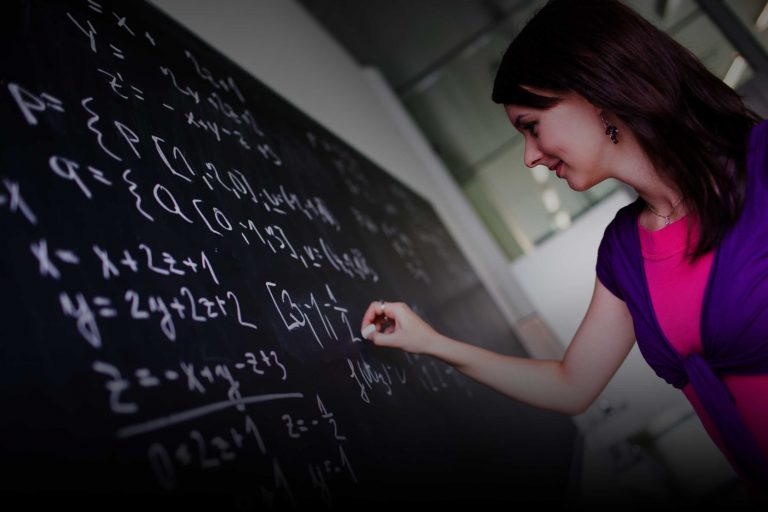 Developing A Theory Of Change | Woman working on a formula on a blackboard